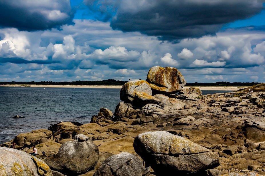The harsh rocky shoreline with the ocean and sandy beach ahead