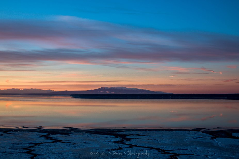 This is a shot of the mountain we call Sleeping Lady which sits across from Anchorage, Alaska during low tide. The winter alpenglow colors are a common pink, purple and blue.