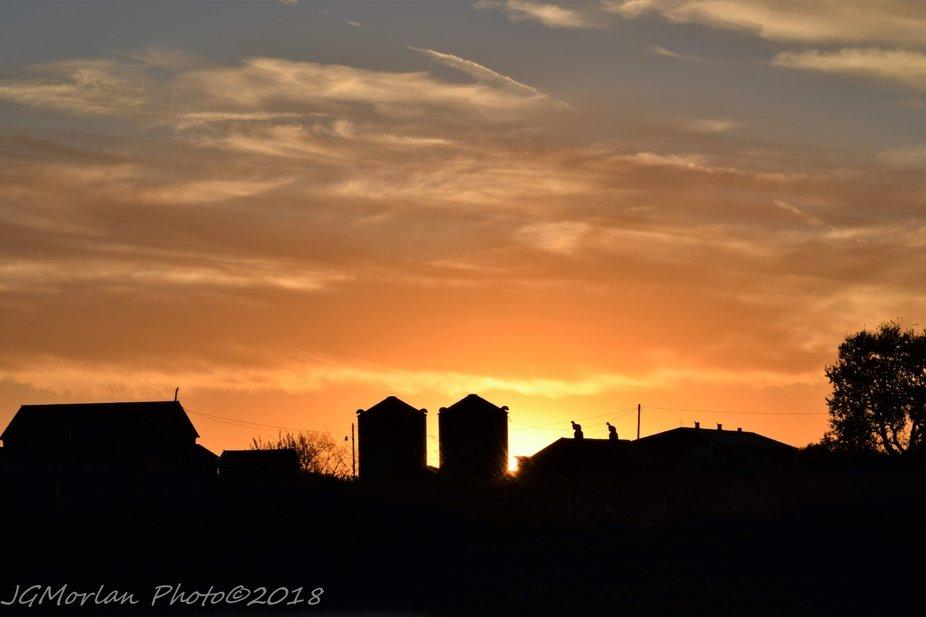 Sun setting behind Midwest farm