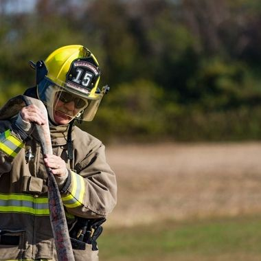 Volunteer fireman empties the hose after putting out a vehicle fire while training.