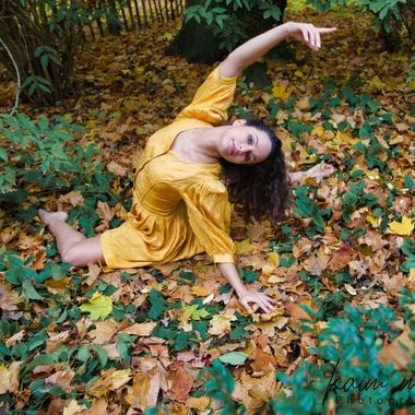 Ballerine warming up surrounded by leaves