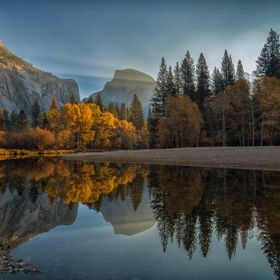 Errant beam of sunlight illuminating the vibrant colors of the autumn trees as the morning breaks over Yosemite valley. The radiance of the sun a...