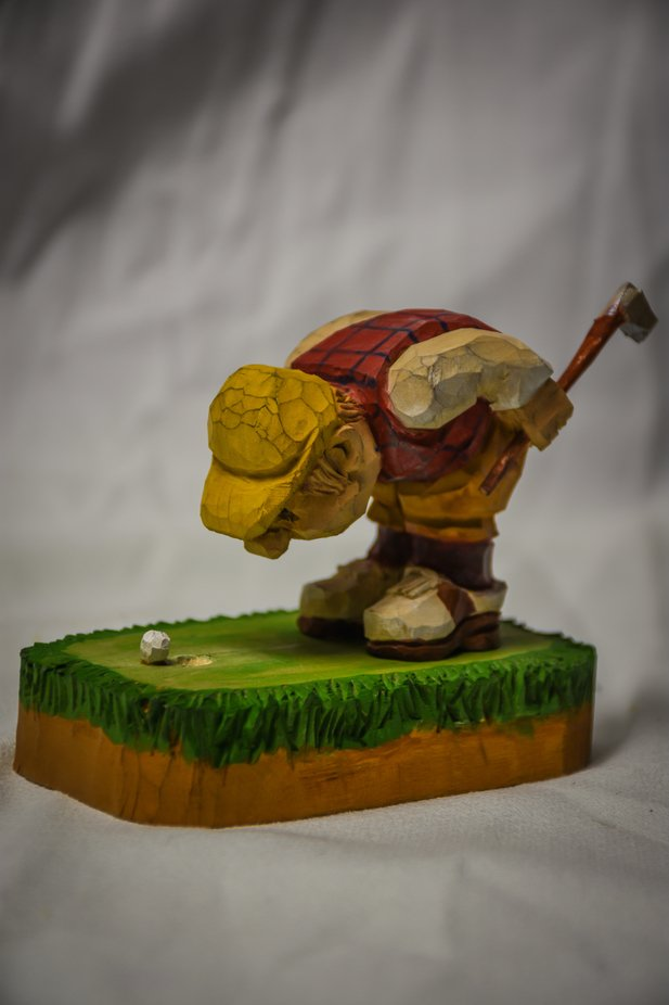 Hand carved sculpture of a golfer.
