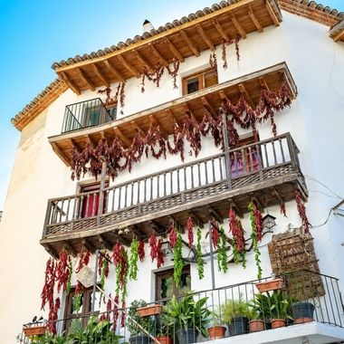 a beautiful house in Cazorla, Spain showing an age old tradition of drying peppers and chillies from their balcony's