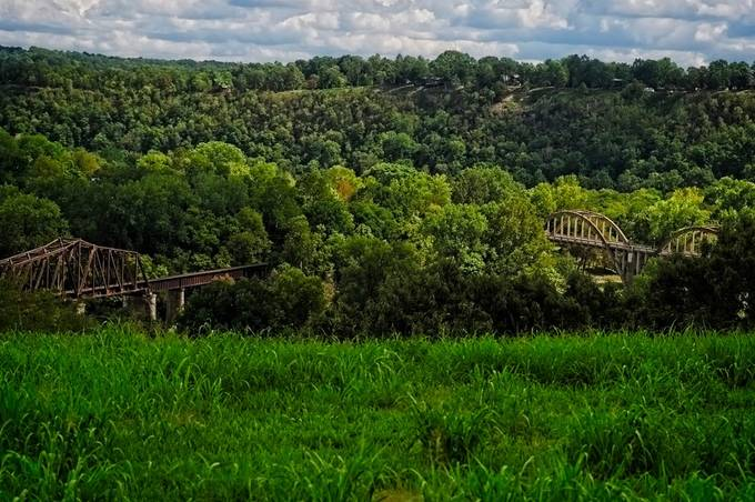 This is not an illusion.  These bridges do seem to go to oblivion.   I first thought it was a mistake,.  but revisiting the site proved that they do indeed cross the river at Cotter, Arkansas, and they do not intersect.