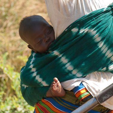 En los poblados rurales de Senegal, no hay guarderias y las madres deben llevar a los bebes consigo, cuando van al pozo a lavar o coger agua.