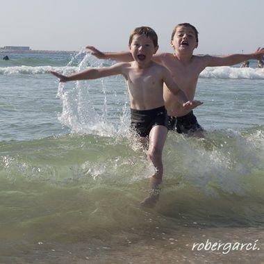 Niños (Hermanos), disfrutando del mar en la playa de Nazaret (Portugal)