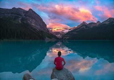 Man sit on rock watching Lake Louise morning clouds with reflections