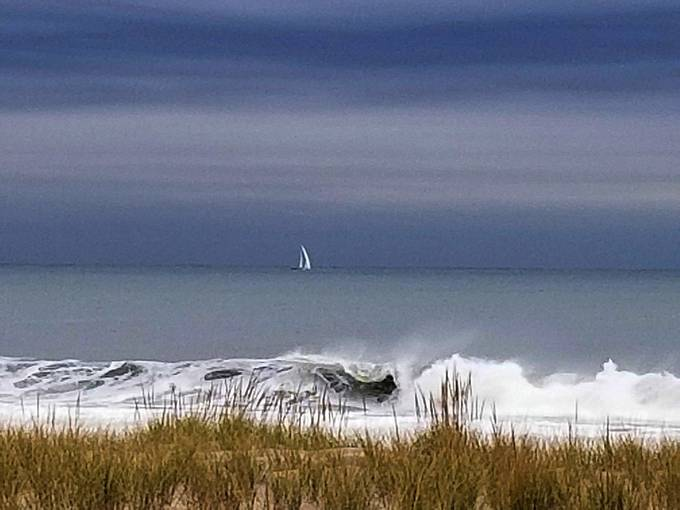 A lone sailboat navigating down the Jersey coastline