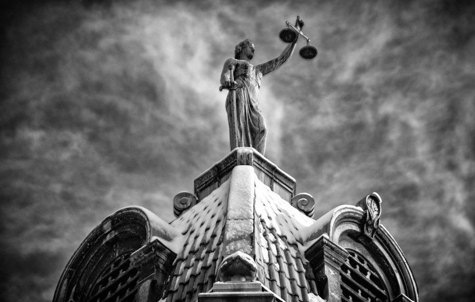 A statue of Lady Justice against swirling clouds