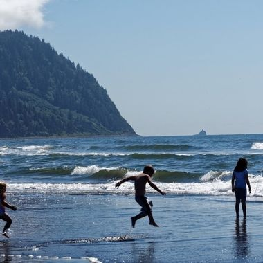 A mother and three children enjoying the surf on the Oregon coast.  The Tillamook Rock lighthouse can be seen in the distance.