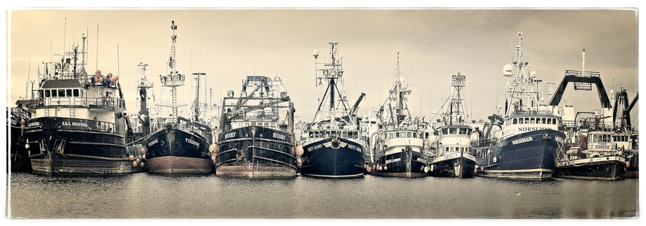 Large boats lined up across the channel from  Fisherman's Wharf in Seattle... The photo is a 4 image panorama with adjusted color and texture to create a little vintage look.