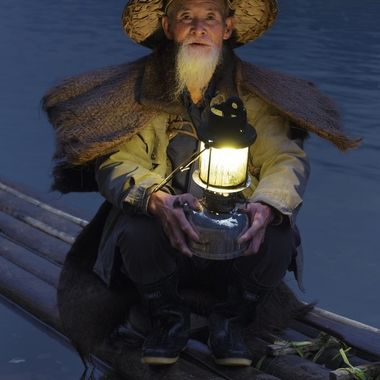 A cormorant fisherman on the Li River near Guilin, southern China. This 87 year old man is the uncle of the 79 year old fisherman whose photo I posted separately. As I was photographing this man before dawn, his brother (another fisherman) rafted across the river to pose for dawn photos at a hotel along the river. All three men have found a better living posing for photos than fishing with cormorants.
