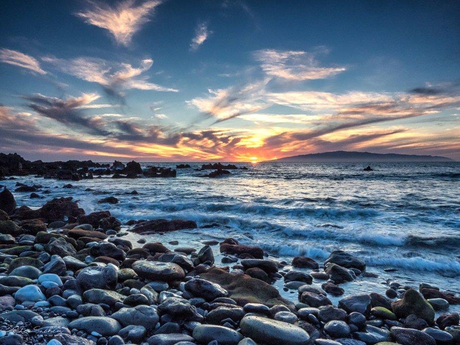 Sunset over La Gomera (Canary Islands) seen from the rocky beach near Guía de Isora - Tenerife.