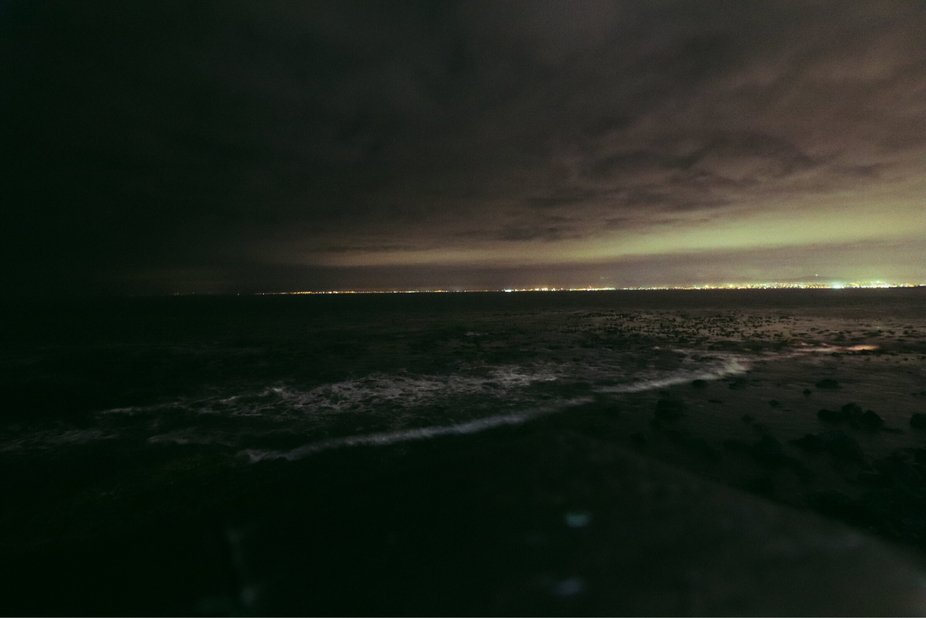 The ocean at night near the cape town waterfront. Lights sparkle on the horizon