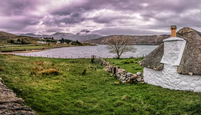A pano of a beautiful white home with a thatched roof.  It was along the road on the Isle of Skye, Scotland, UK