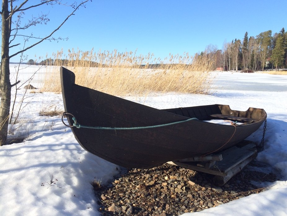 boat on shore at a frozen lake in Finland