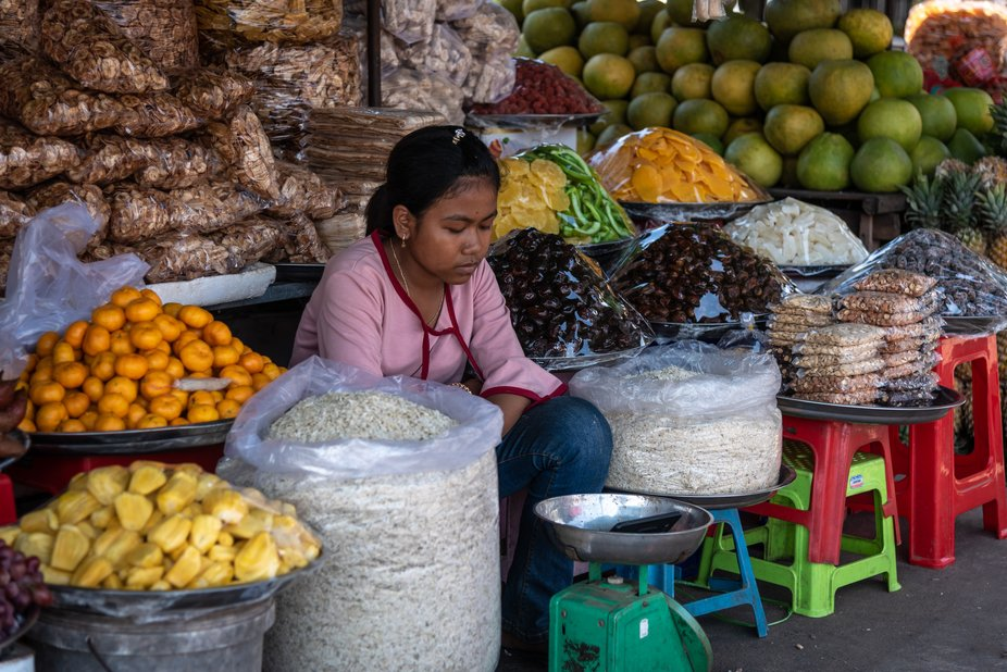 on a market in Cambodia, this young girl is watching her smart phone
