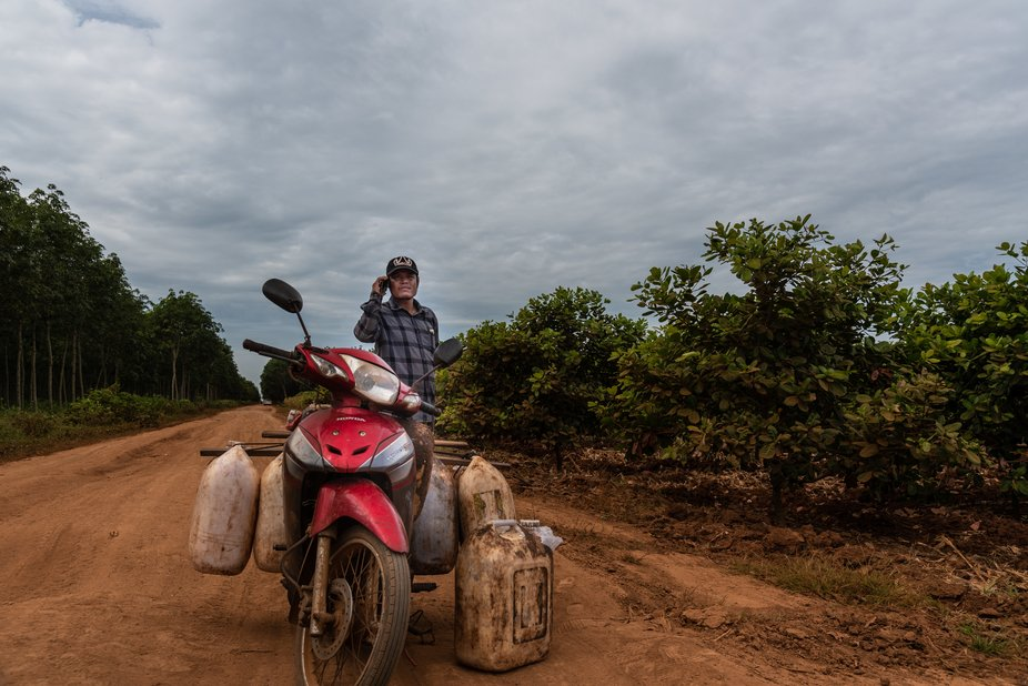 In the middle of nowhere in between plantations the motorbike of  this man carrying cans of rubbe...