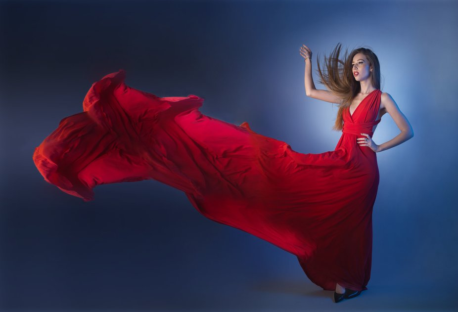 Model wearing a long red flowy gound in the studio