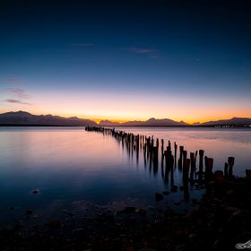 The city of Puerto Natales and one of its old piers while the sun is fading over the mountains and the last lights of the day are giving away the...