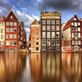 The colors and architecture of Amsterdam are reflected in the waters of the Damrak canal.