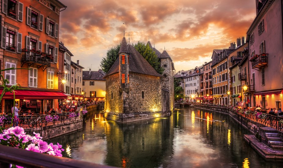 A colorful sunset over the canal in the historic Old Town of Annecy, France.