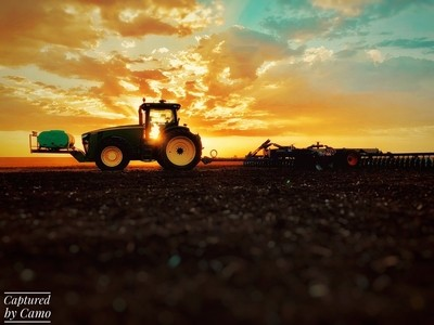 Burning daylight. Tractor in the summer afternoon sunset.