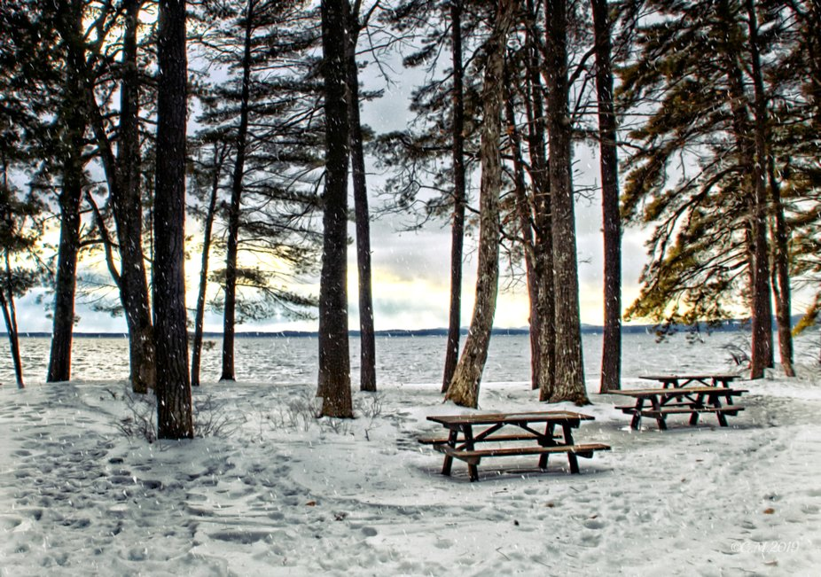 Picnic tables lay unused due to a blanket of snow at Sebago lake park in Maine.