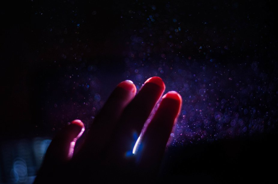 Hand against purple and blue lights