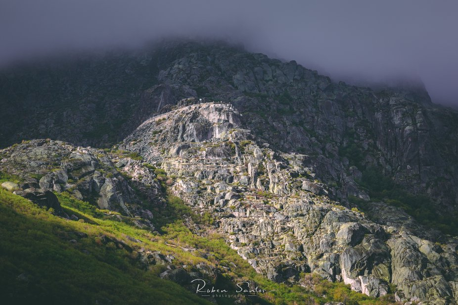 Small gape between the clouds allowing the sun light to illuminate part of the cliff face of Estr...