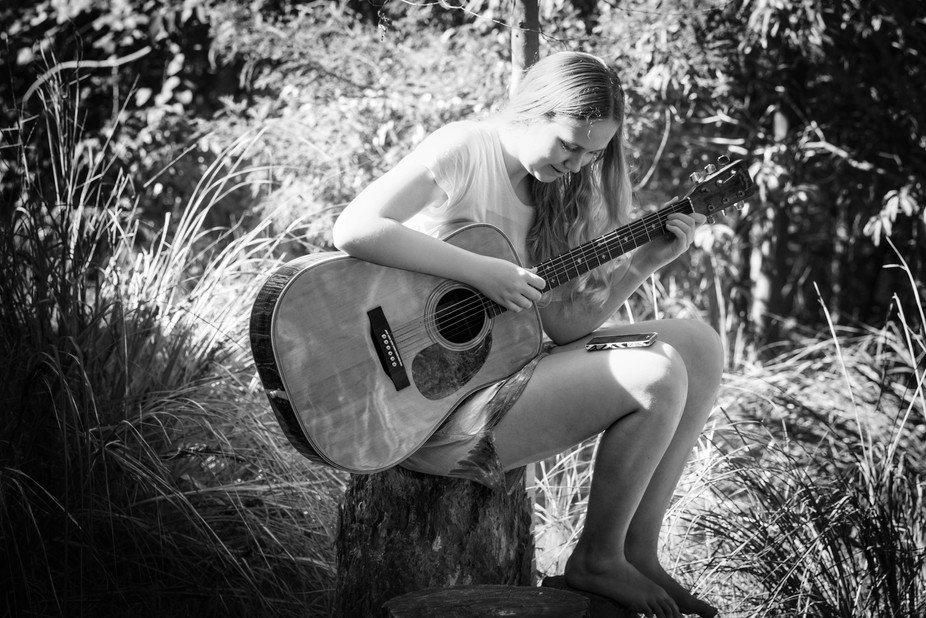 A young musician enjoying nature and a peaceful afternoon takes time out to practice her music