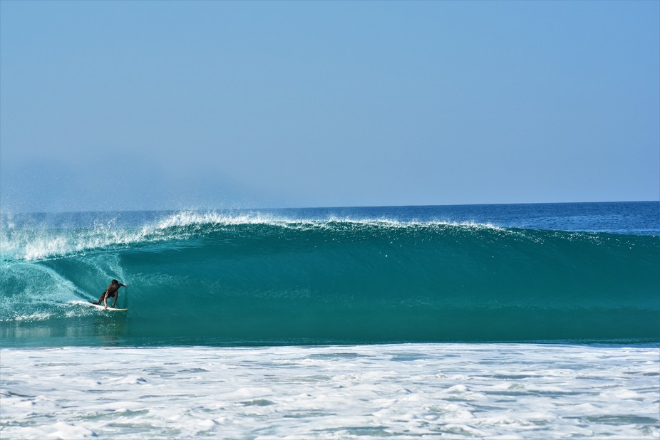 surfer entering a barrel with so much confidence to be able to touch the side of the wave with hi...