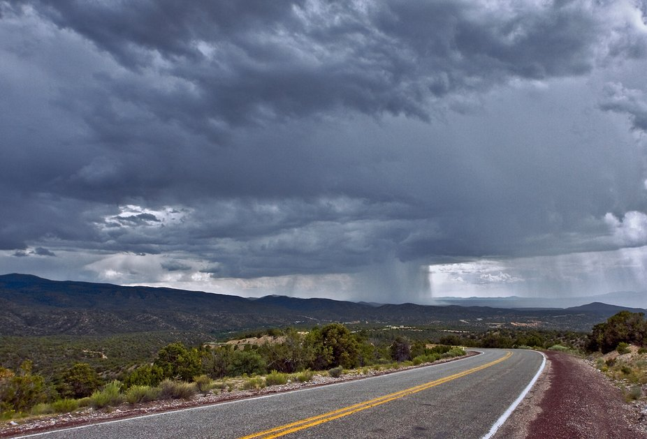The large rainshaft, from a July monsoon storm, is providing Northern New Mexico's Nambé reservation with much needed moisture. In the distance is the Rio Grande Valley.