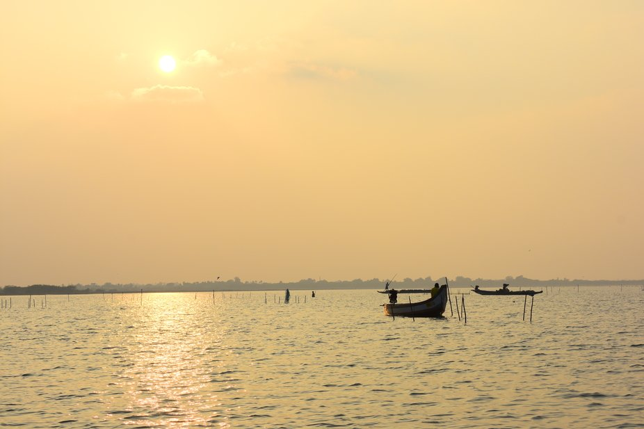 a beautiful sunset on a lake, while fishermen carry out their fishing activity.