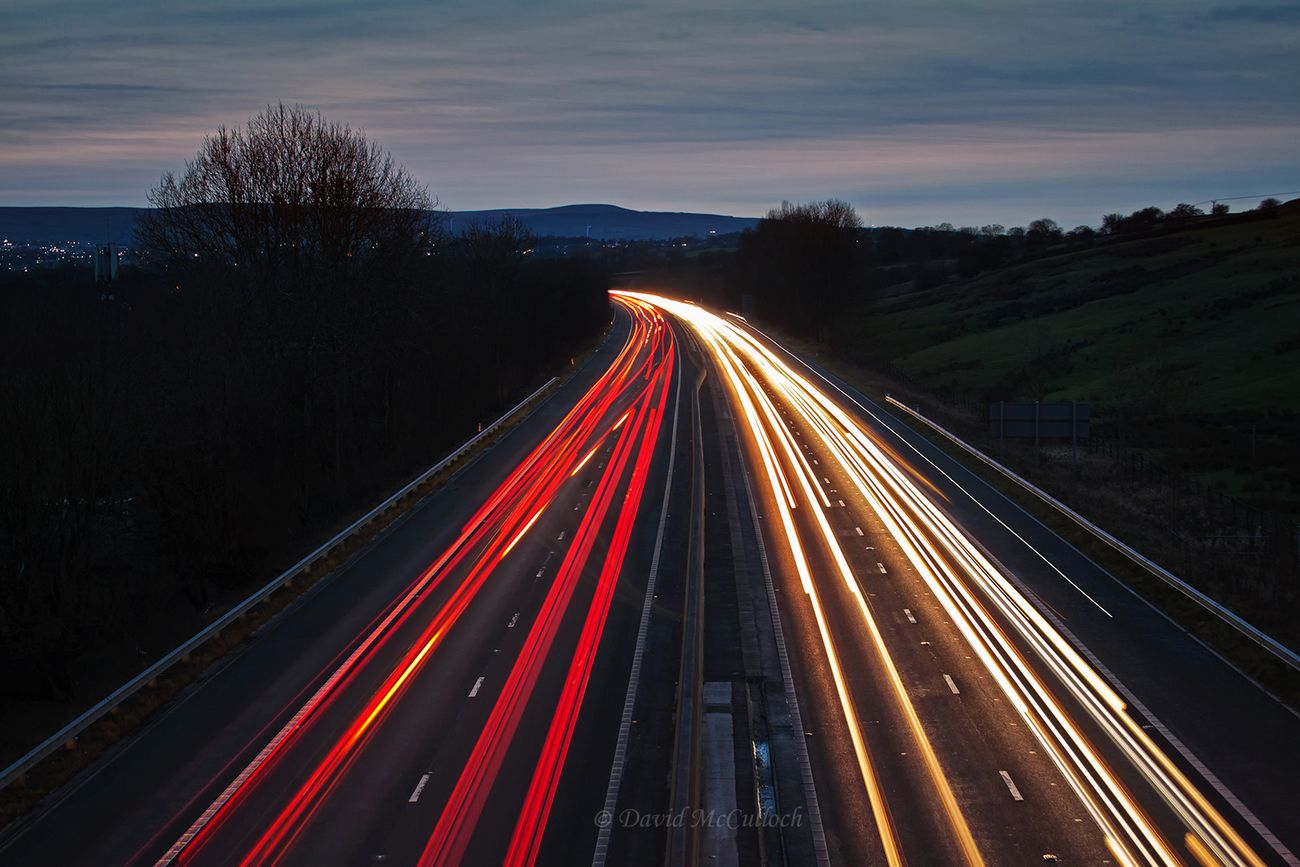 Tails of light made by traffic at dusk on a local motorway