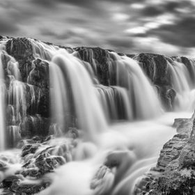 60 second exposure of kolugljüfur wayerfalls in iceland at high noon while surrounded by a constant  swarm of plague size, black flies.