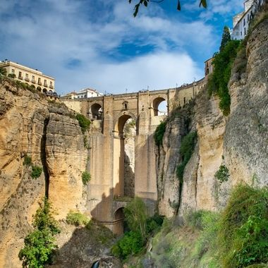 this a is shot taken of the main bridge which is found in Ronda, Spain. the bridge connects both sides of the town over a small river and waterfall beneath