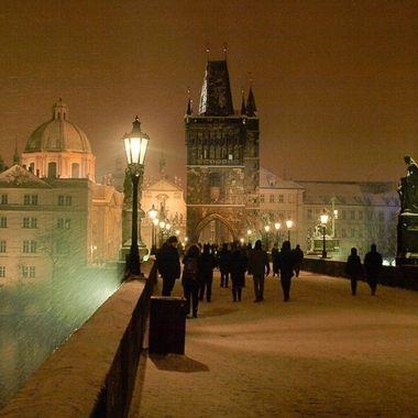 Vista nocturna del Puente principal de Praga sobre el rio Moldava, en plena nevada.