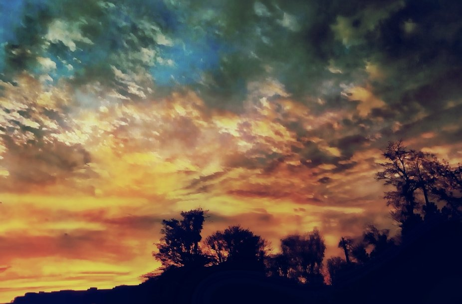 Striking and dramatic cloud formations reflect the intense red, orange and yellow hues of a fiery...