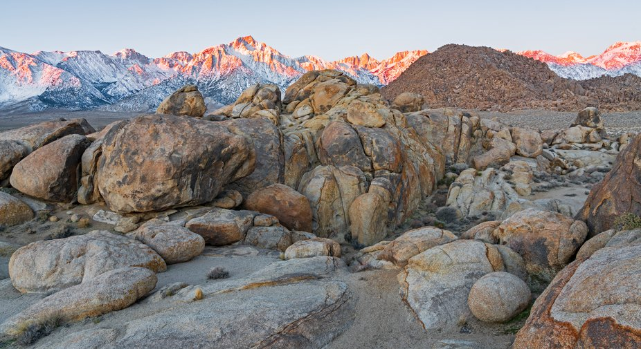 the sun is rising over the mountains in Alabama Hills,turning the peaks of Mt Whitney and Lone Pi...
