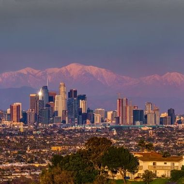 This photo was stitched together from 5 images.  The moisture in the air in Southern California varies.  When the condition is just right, the sunlight before sunset casts a pinkish purple color on the moisture layer as well as the snow capped San Gabriel Mountains (the peak of Mount Baldy being the highest one) in the background some 45 miles east of downtown Los Angeles.  The vantage point for this view is at the top of Kenneth Hann State Recreation Area in Baldwin Hills, LA.