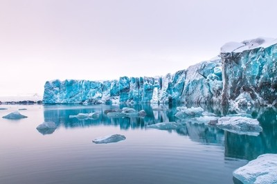 Glacier breaking off into the Jökulsárlón glacier lagoon with icebergs drifting towards the ocean during sunset. This shot was taken at the northern end of the lagoon after a bumpy off-road ride across icy and snowy terrain, followed by a 1.5 hours hike w