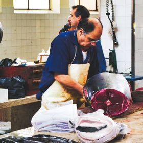 At the fish market, carving a fresh tuna.