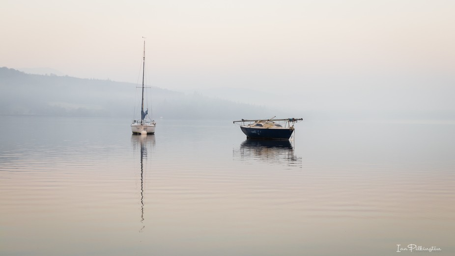 2 boats silently waiting in the morning mist