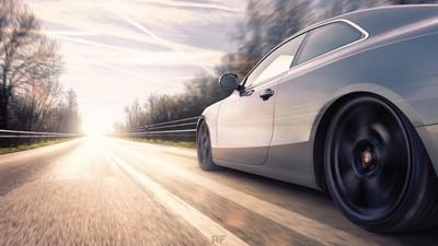 A car drives on a road towards the sun.