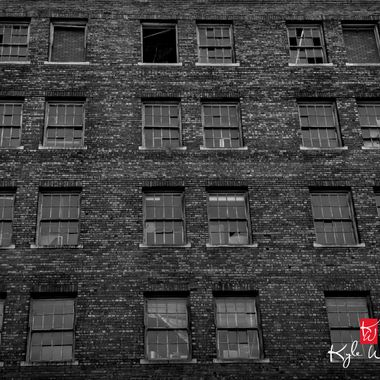 Black and white windows on a warehouse, I would guess it's abandoned because some windows are busted out, but I can't really tell