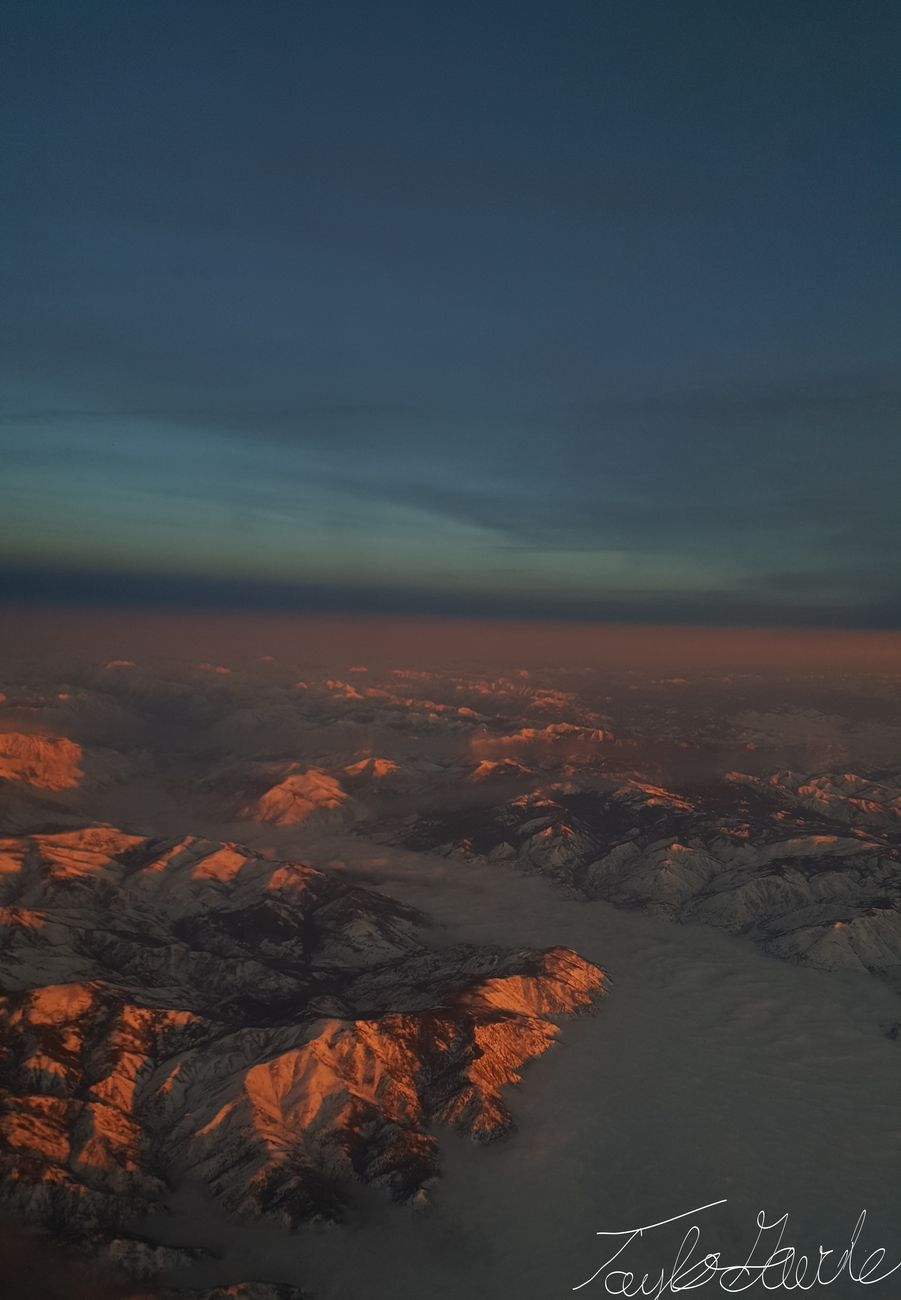 From high above the tree tops, the mountains say hello with a beautiful glow.