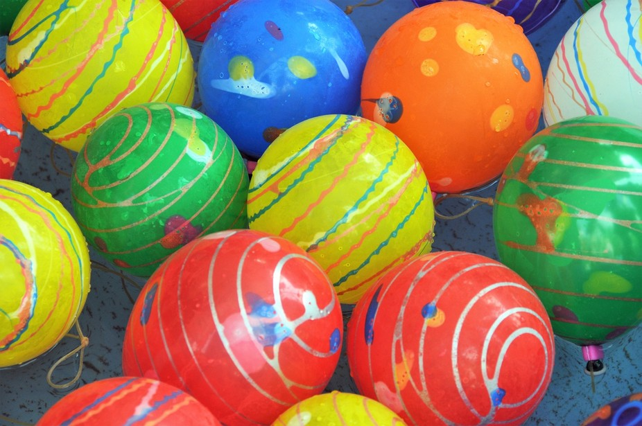 Picking up colourful water-filled balloons with hooks on tissue-paper lines is a common game at J...