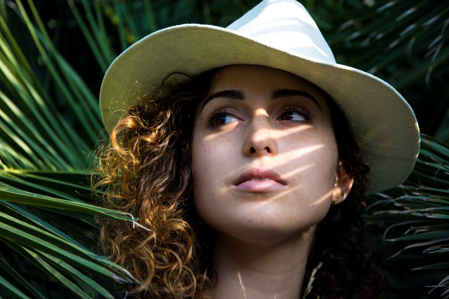 portrait of woman with a hat between light and shadow of a palm tree
